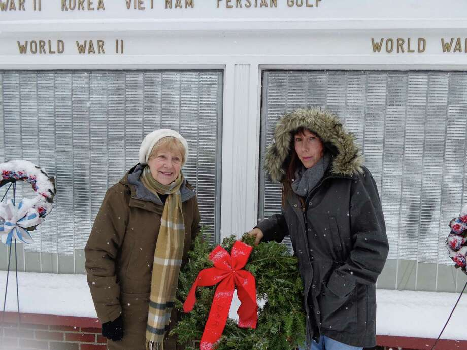 WREATH HONORS VETERANS The Eunice Dennie Burr Chapter of the Daughters of the American Revolution placed a holiday wreath at the Veterans Memorial on the Fairfield Town Green on Saturday Dec. 14 as part of nationwide program to honor veterans. Wreaths Across America was founded by a commercial wreathmaker in Maine that donates wreaths for placement at Arlington National Cemetery, and the program encourages local communities to participate. Local DAR members Pamela Huth, left, and Debra Pungys placed the Fairfield wreath in  brief ceremony. Photo: Contributed Photo / Fairfield Citizen contributed
