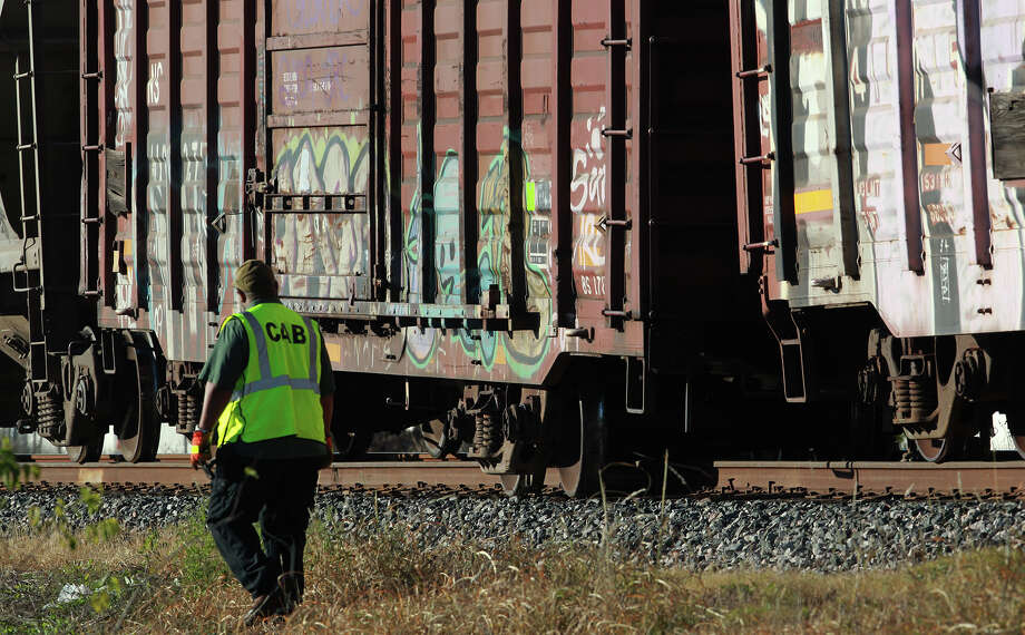A railrod worker walks past a boxcar that derailed Tuesday morning December 17, 2013 on a northbound Union Pacific freight train. The section of track runs parallel to I-35 near Walzem Road and blocked traffic on Walzem during morning rush hours. Another car on the train also derailed. Photo: JOHN DAVENPORT, SAN ANTONIO EXPRESS-NEWS / ©San Antonio Express-News/Photo may be sold to the public