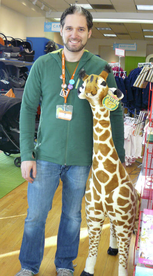 Eli Gurock poses with a friendly stuffed giraffe in his new store, Magic Beans. Gurock and his wife, Sheri, own five Magic Beans stores. The other four are in the Boston area. Photo: Staff Photos/Gretchen Webster / Fairfield Citizen