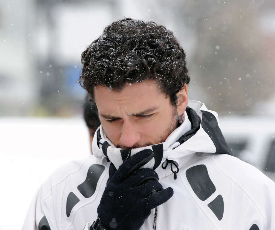 Alex Shuaib covers-up from the snow as he walks along Greenwich Avenue during the storm that hit Greenwich, Conn., Tuesday afternoon, Dec. 17, 2013. Shuaib works in Greenwich. Photo: Bob Luckey / Greenwich Time