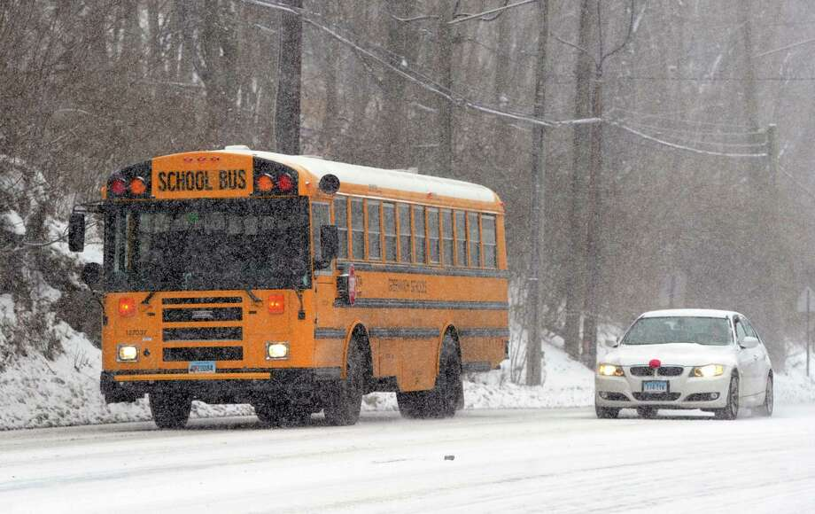 A bus and car slowly move up a hilly section of West Putnam Avenue during the snow storm that hit Greenwich, Conn., Tuesday afternoon, Dec. 17, 2013. Photo: Bob Luckey / Greenwich Time