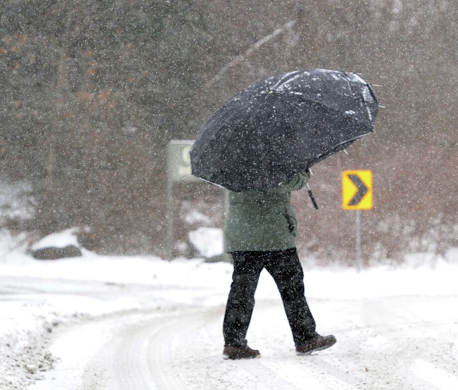 A man walking on Holly Hill Lane uses an umbrella during the snow storm that hit Greenwich, Conn., Tuesday afternoon, Dec. 17, 2013. Photo: Bob Luckey / Greenwich Time