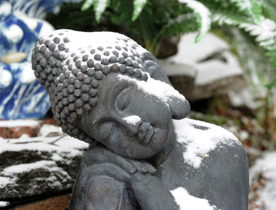A snow-covered statue on the front lawn of a Chickahominy home during the snow storm that hit Greenwich, Conn., Tuesday afternoon, Dec. 17, 2013. Photo: Bob Luckey / Greenwich Time