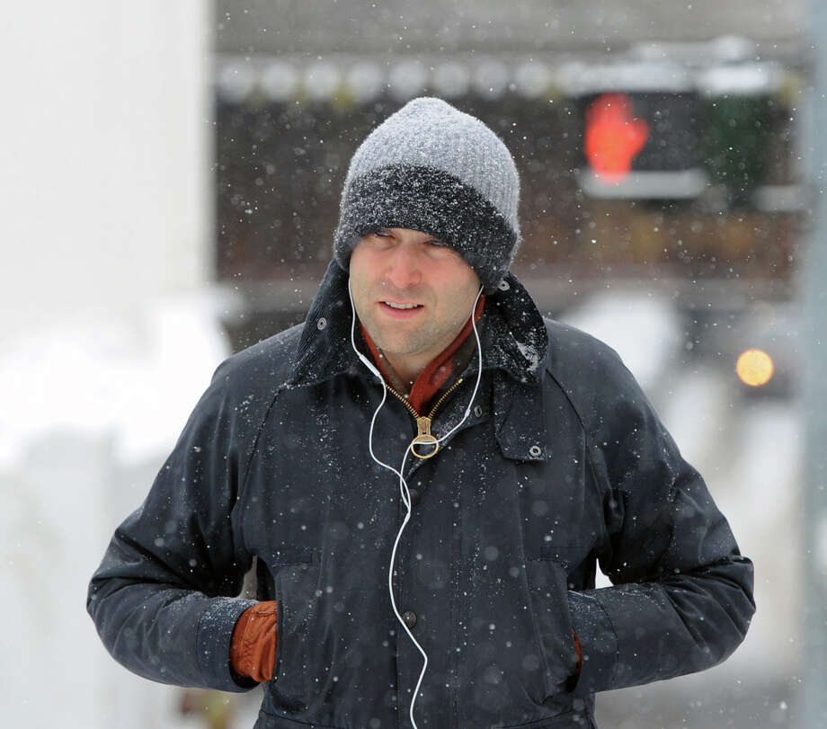 A man crosses Railroad Avenue during the snow storm that hit Greenwich, Conn., Tuesday afternoon, Dec. 17, 2013. Photo: Bob Luckey / Greenwich Time