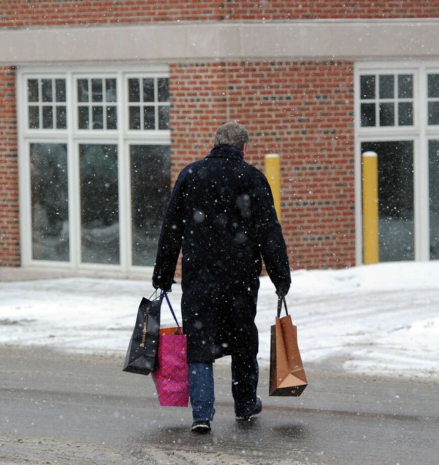A man carrying shopping bags makes his way across Greenwich Avenue during the snow storm that hit Greenwich, Conn., Tuesday afternoon, Dec. 17, 2013. Photo: Bob Luckey / Greenwich Time