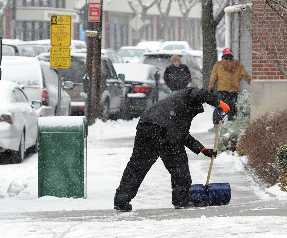 A man shovels snow from the sidewalk along Railroad Avenue during the snow storm that hit Greenwich, Conn., Tuesday afternoon, Dec. 17, 2013. Photo: Bob Luckey / Greenwich Time