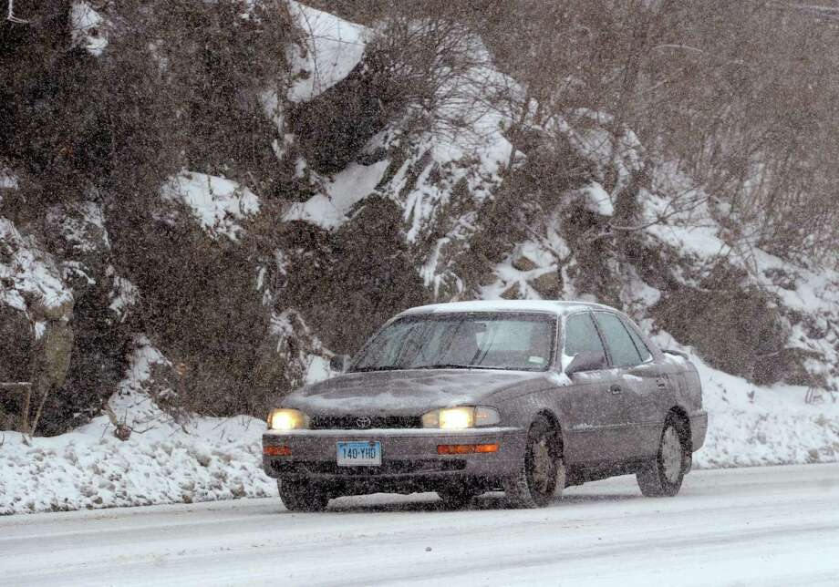 A car slowly moves up a hilly section of West Putnam Avenue during the snow storm that hit Greenwich, Conn., Tuesday afternoon, Dec. 17, 2013. Photo: Bob Luckey / Greenwich Time