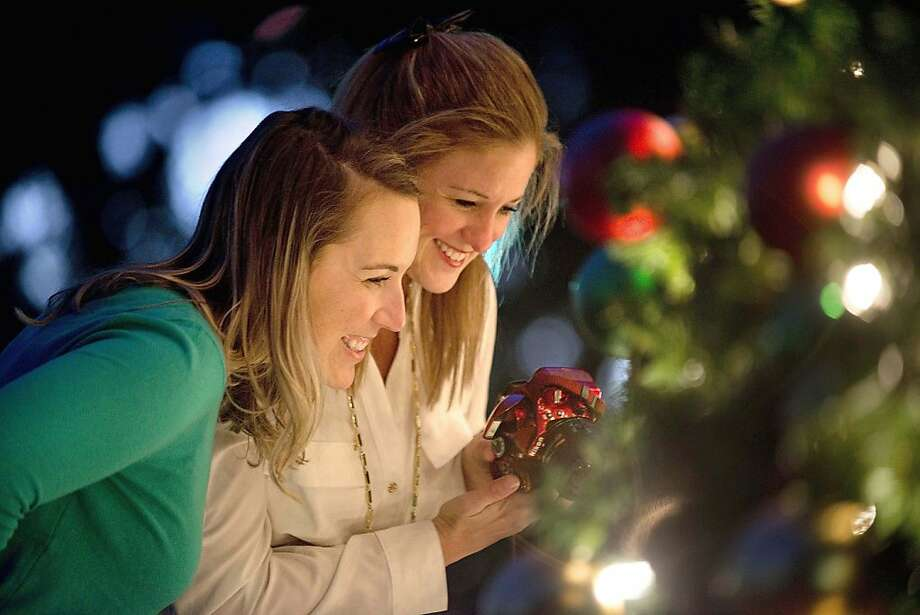 Double selfie: Ashley Pepe (left) and Ann Marie Wilson take a photo of their reflection on an ornament on the Fort Landing park Christmas tree 