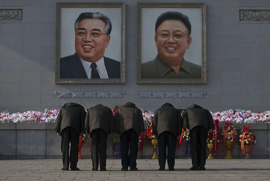 North Koreans bow beneath portraits of the late leaders Kim Jong Il and Kim Il Sung in Pyongyang on Tuesday, Dec. 17, 2013. Across the capital city, North Koreans observed the second anniversary of the death of Kim Jong Il. (AP Photo/David Guttenfelder) Photo: David Guttenfelder, Associated Press
