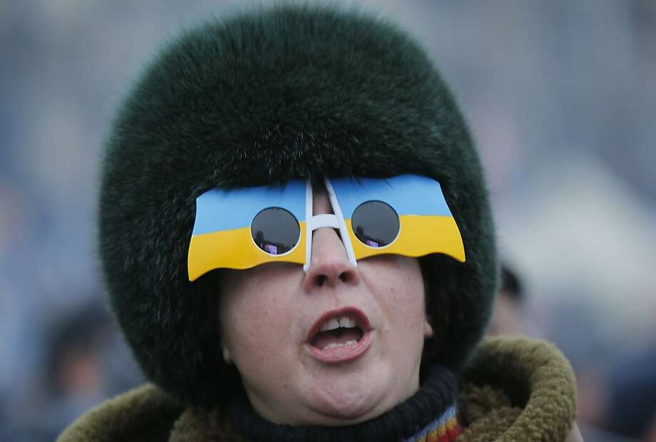 A Pro-European Union activist in sunglasses in Ukrainian national colors shouts during a rally in the Independence Square in Kiev, Ukraine, Tuesday, Dec. 17, 2013. Weeks of angry pro-European Union protests as well as Western pressure have forced Yanukoyvch to make some concessions to the opposition. Last week Yanukovych called for an amnesty for some of the activists detained. (AP Photo/Dmitry Lovetsky) Photo: Dmitry Lovetsky, Associated Press