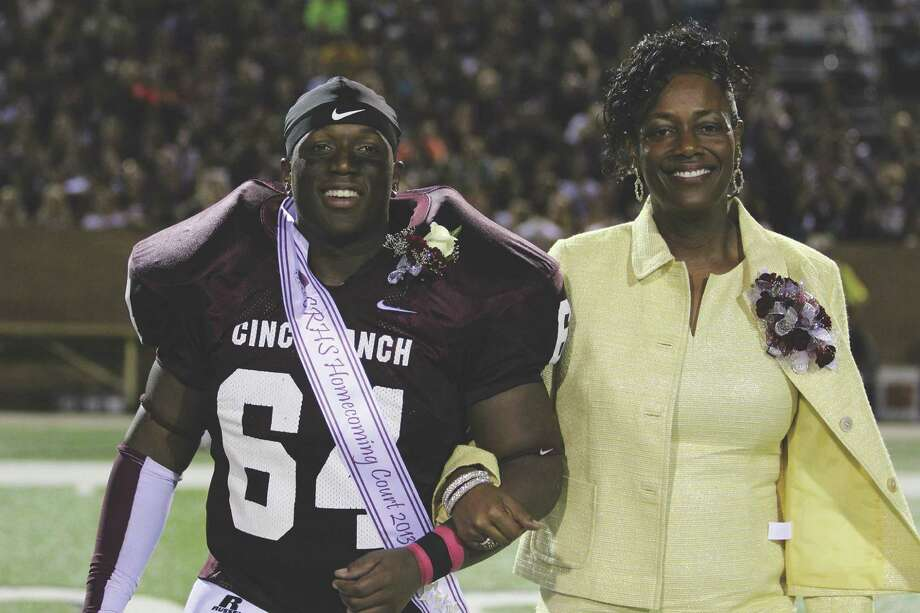 Tony Smith, who was named to the Cinco Ranch High School Homecoming Court, escorts his mom, Angela Smith, across the football field. He was later crowned as homecoming king. Photo: Eilidh Gill