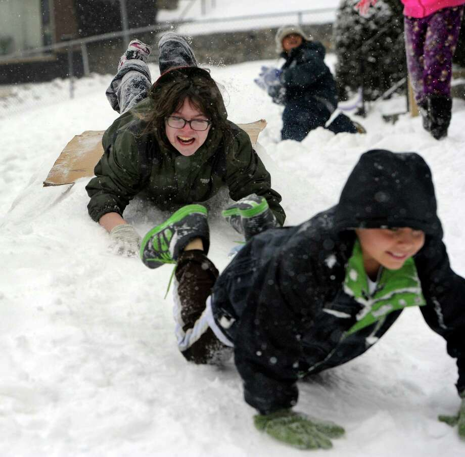 Kira Coello, 13, left, and Brian Ortega, 11, slide down a make-shift hill they and other neighborhood kids made for playing in the snow on Merrimac Street in Danbury, Conn. Tuesday, Dec. 17, 2013. Photo: Carol Kaliff / The News-Times