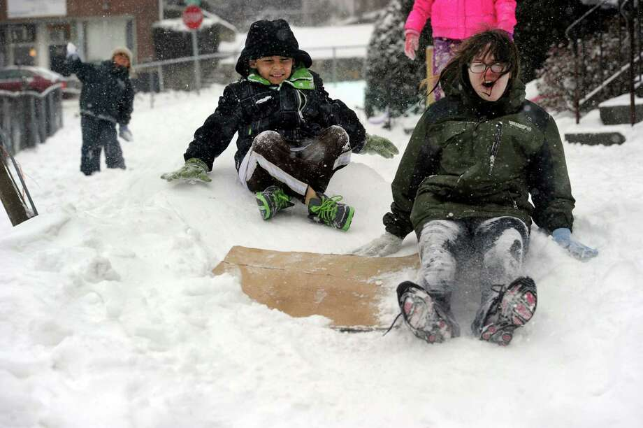 Brian Ortega, 11, left, and Kira Coello, 13, slide down a make-shift hill they and other neighborhood kids made for playing in the snow on Merrimac Street in Danbury, Conn., Tuesday, Dec. 17, 2013. Photo: Carol Kaliff / The News-Times