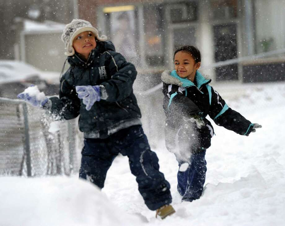 Brandon Ortega, 9, left and Joselyn Velez, 7, playn in the snow on Merrimac Street in Danbury, Conn. Tuesday, Dec. 17, 2013. Photo: Carol Kaliff / The News-Times