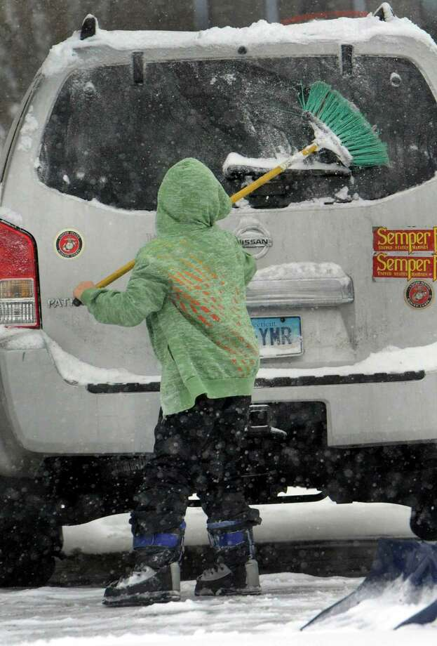 Marco Ochoa, 8, sweeps snow from the family car in Danbury, Conn. Tuesday, Dec. 17, 2013. Photo: Carol Kaliff / The News-Times