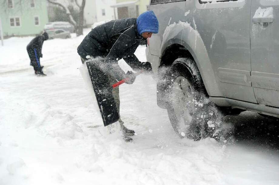 Andres Almanzar, 14, clears snow away from the family car in Danbury, Conn. Tuesday, Dec. 17, 2013. Photo: Carol Kaliff / The News-Times