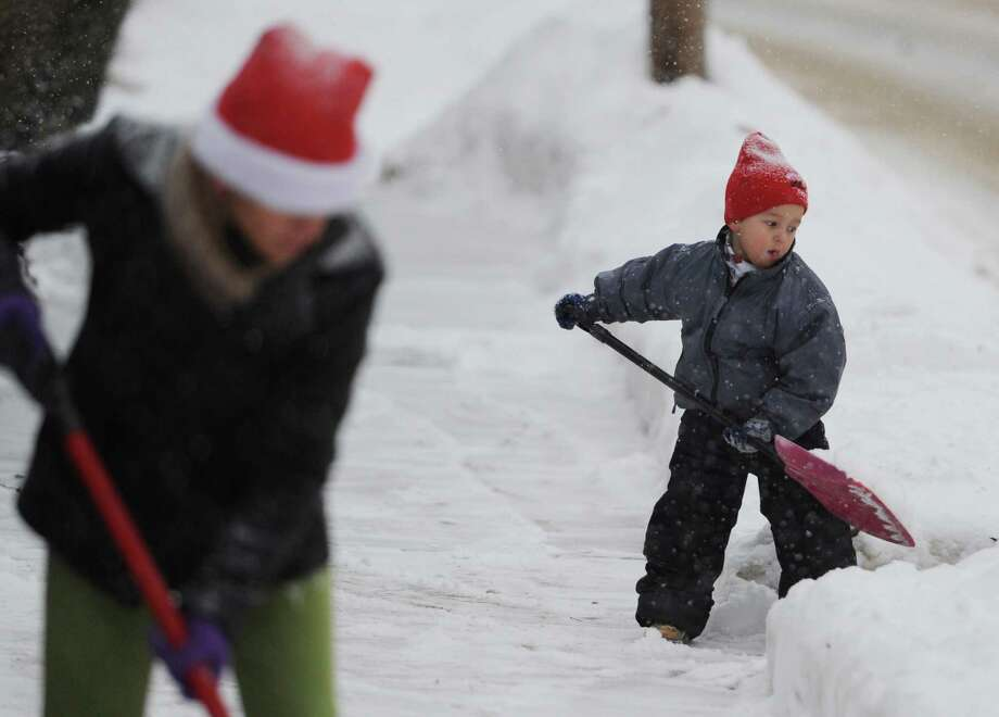 Gabriel Oliver, 4, helps his mother, Celia Oliver, shovel snow on the sidewalk outside their home along Osborne Street in Danbury, Conn. on Tuesday, Dec. 17, 2013. Photo: Tyler Sizemore / The News-Times