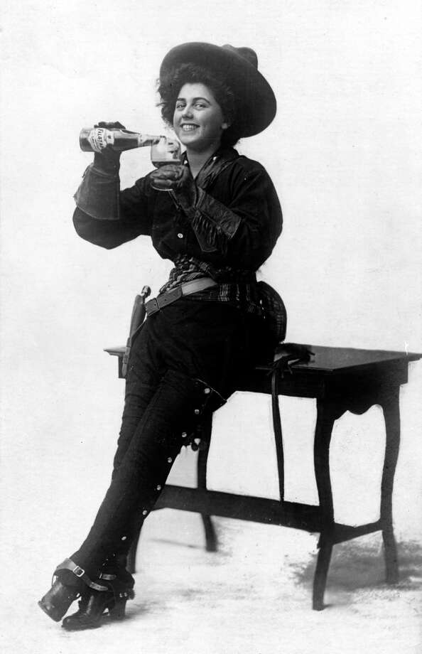 Cropped ad for Falstaff Beer features a woman dressed as a cowgirl as she pours a glass of beer while she sits on the edge of a table, early 1900s. Photo: Vintage Images, Getty Images