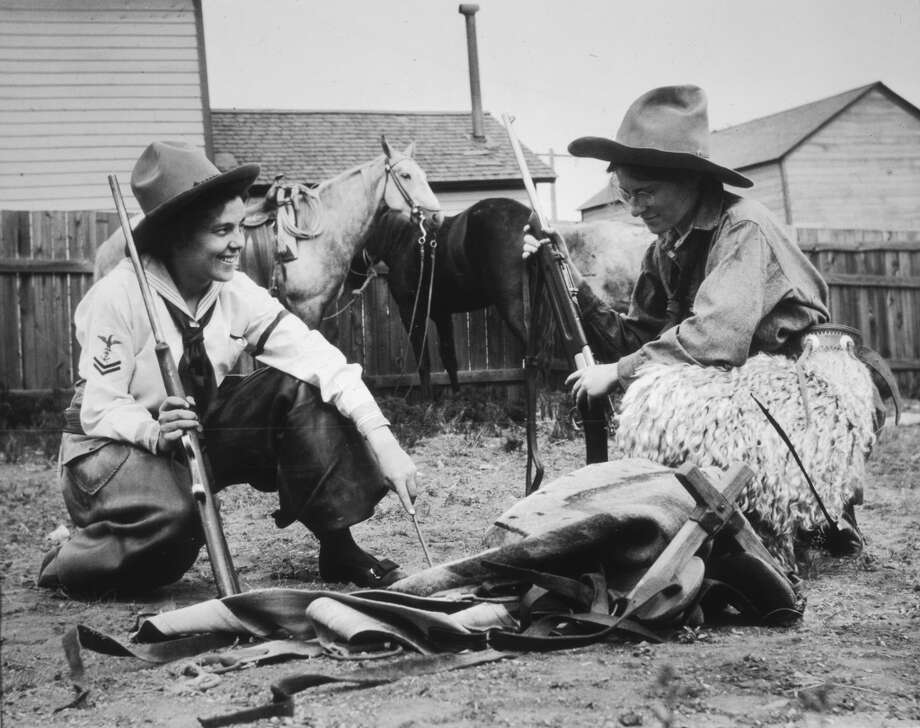Two cowgirls smile while crouching with rifles in front their horses, Northern Wyoming, 1920. Photo: Historic Photo Archive, Getty Images