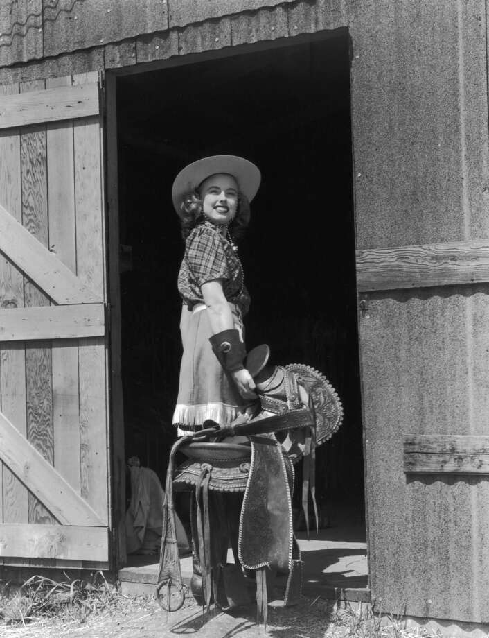 A young woman looks back and smiles as she stands in the doorway of a stable, holding a horse's saddle, 1945.  Photo: Hulton Archive, Getty Images