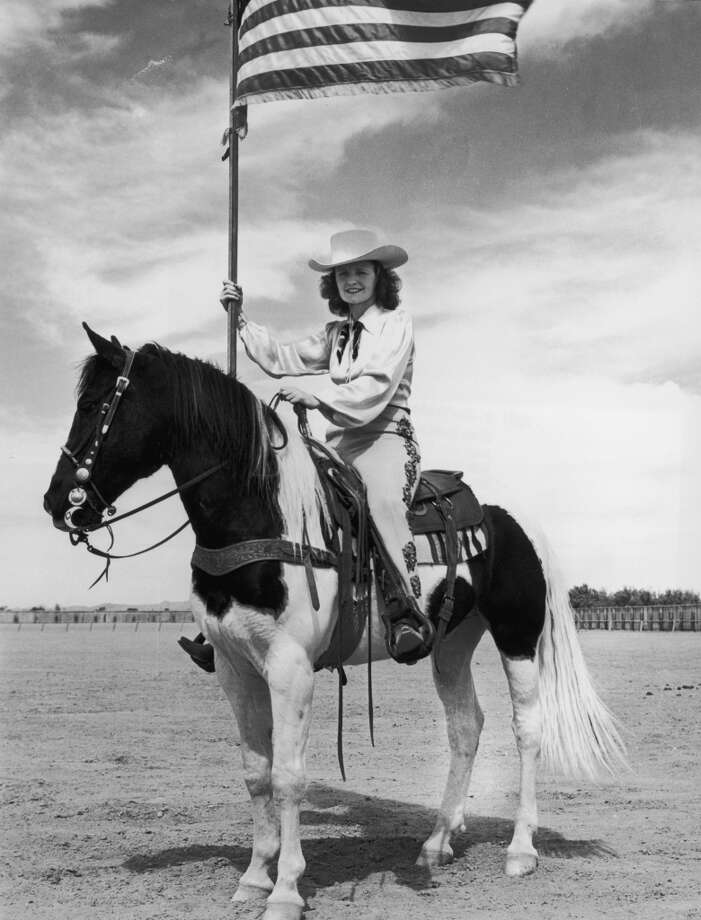 Portrait of a cowgirl holding a flag on horseback, 1945. Photo: Lambert, Getty Images