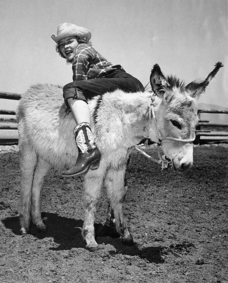 A young cowgirl climbs up on her donkey backwards, Las Vegas, Nevada, 1947. Photo: Underwood Archives, Getty Images