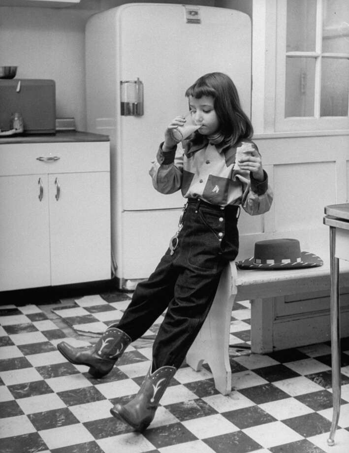 Young girl wearing cowgirl outfit (including boots) drinking milk and eating sandwich in kitchen, 1948 . Photo: Nina Leen, Time & Life Pictures/Getty Image