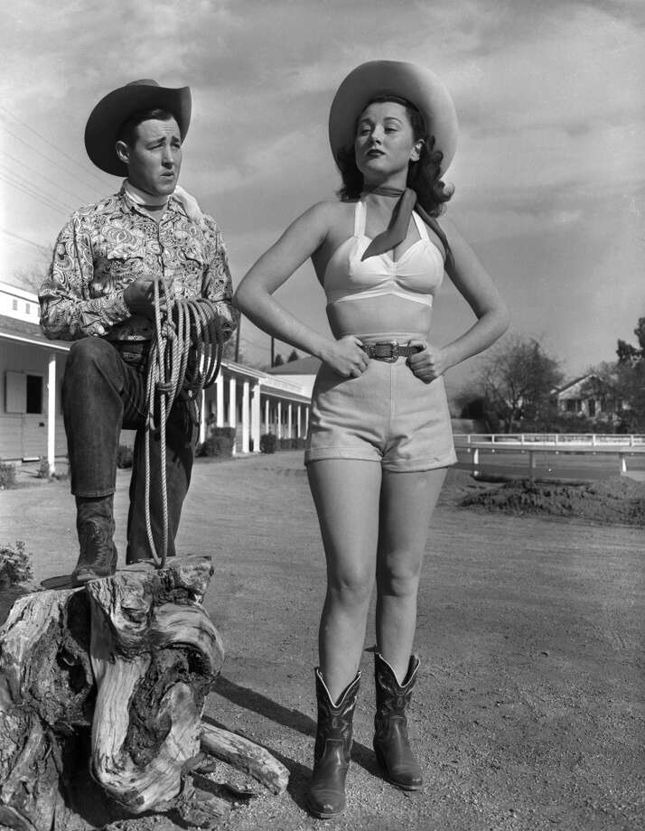 American actor Wayne Burson in a cowboy costume holds a lasso while watching Wendy Waldron dressed in a cowgirl outfit in a parking lot, 1949. Photo: Hulton Archive, Getty Images