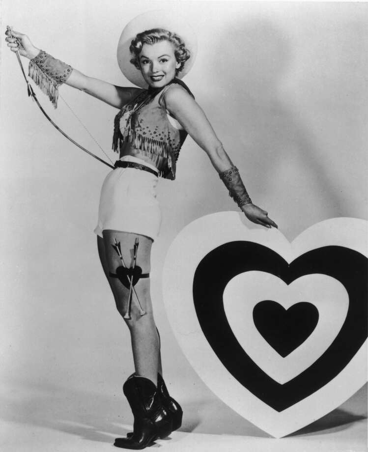 Marilyn Monroe (1926 - 1962) leaning on a heart-shaped target and holding a bow, 1952.  Photo: Hulton Archive, Getty Images