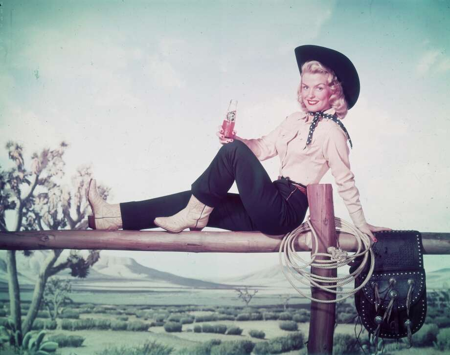 Full-length portrait of a woman dressed as a cowgirl sitting on top of a fence and holding a soda-pop bottle, 1955.  Photo: Tom Kelley Archive, Getty Images