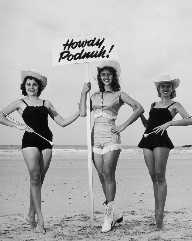 Three young women, wearing cowgirl costumes, hold batons and a sign while posing on a beach during a 'Sandy Shoes Festival, Fort Pierce, Florida, 1955.  Photo: Hulton Archive, Getty Images