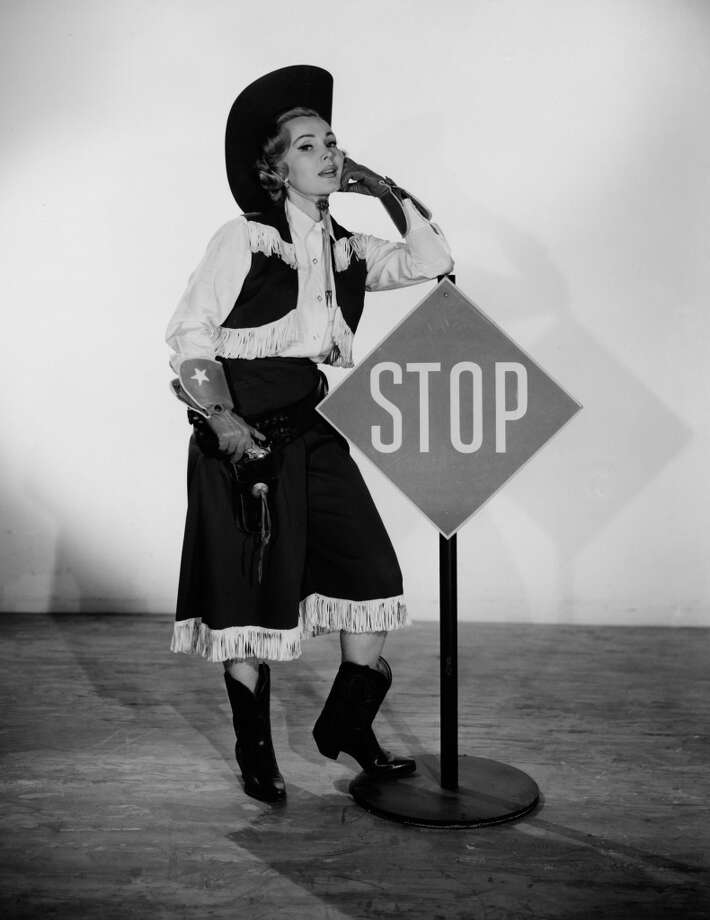 Hungarian actress Zsa Zsa Gabor poses leaning against a stop sign dressed in a cowgirl costume, September 17, 1958. Photo: CBS Photo Archive, Getty Images
