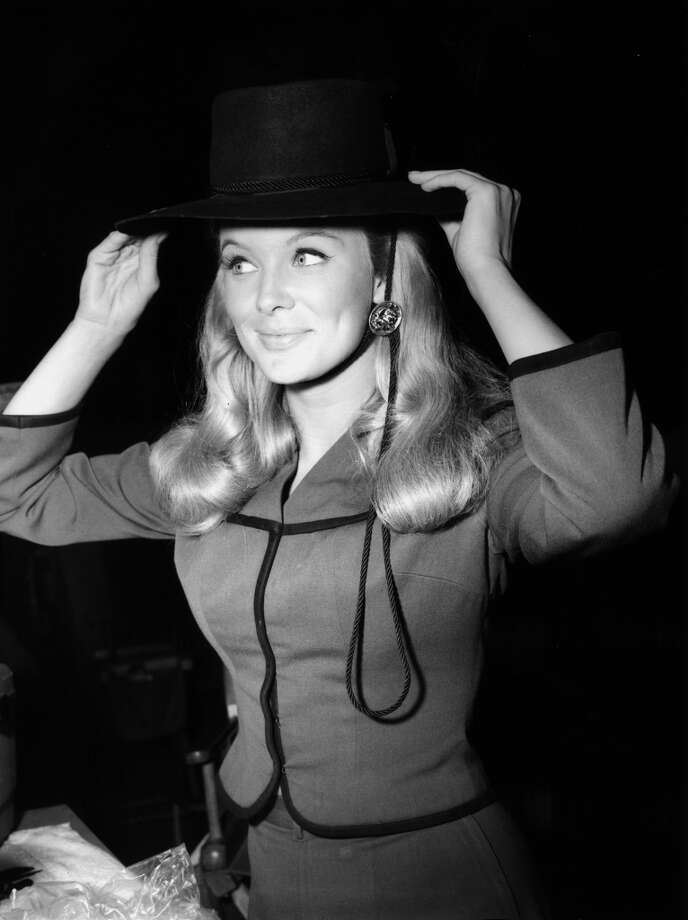 American actor Linda Evans smiles while trying on a wide-brimmed hat, possibly on the set of the television series, 'The Big Valley', 1967.  Photo: Hulton Archive, Getty Images