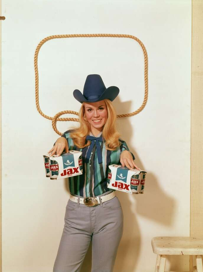 Portrait of a model in a oversize stetson and a striped shirt with a Western string tie as she holds a six-pack of Jax brand beer cans in each hand, January 1969. Photo: Tom Kelley Archive, Getty Images
