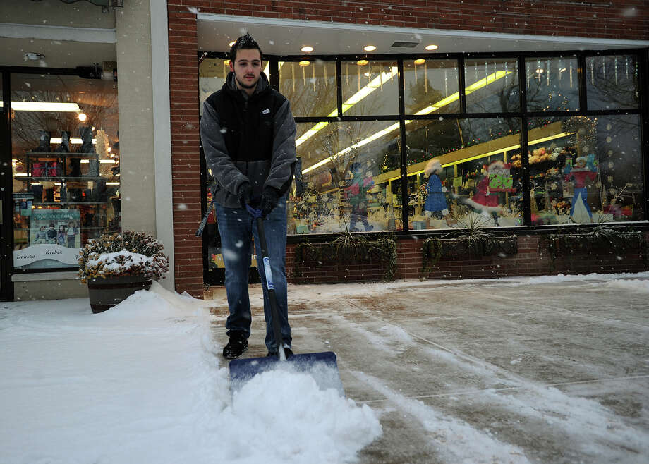 Dan Martins, of Milford, shovels the snow for the fourth time in one day outside Howe's Drug on Broad Street in downtown Milford, Conn. on Tuesday, December 17, 2013. Photo: Brian A. Pounds / Connecticut Post