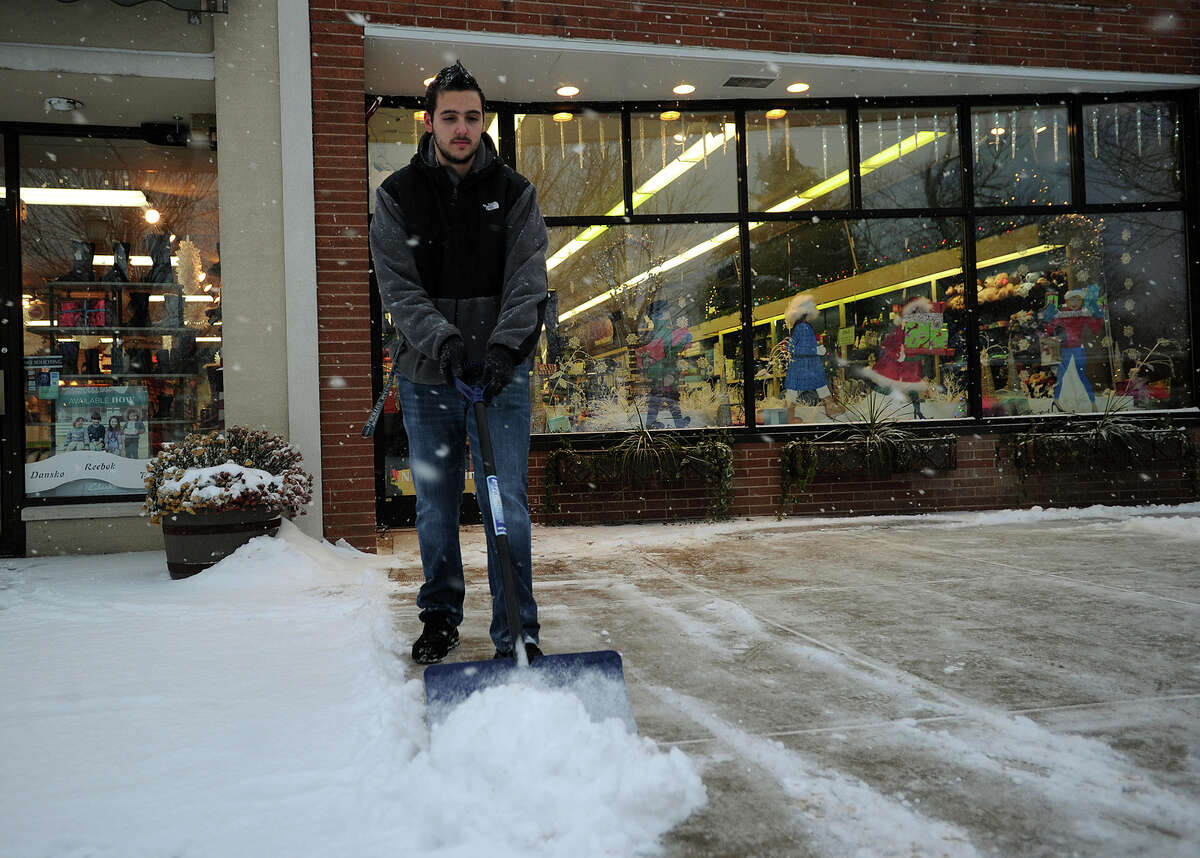 Dan Martins, of Milford, shovels the snow for the fourth time in one day outside Howe's Drug on Broad Street in downtown Milford, Conn. on Tuesday, December 17, 2013.