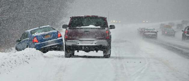 A car off the road on the Northway as a steady snow falls Tuesday Dec. 17, 2013, in Colonie, NY.  (John Carl D'Annibale / Times Union) Photo: John Carl D'Annibale / 00025077A