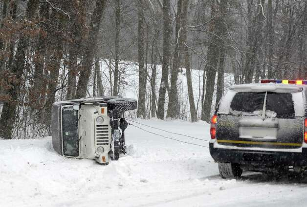 A jeep is winched from the median near Exit 24 Dec. 17, 2013 in Albany, N.Y. after the driver lost control.   (Skip Dickstein / Times Union) Photo: Skip Dickstein / 00025076A
