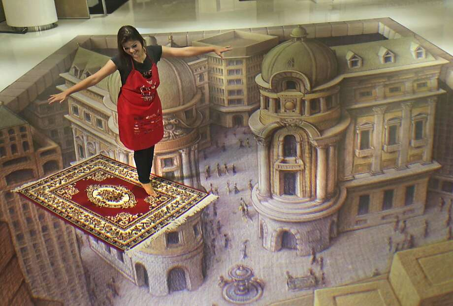 "Flight of fancy:A woman ""rides"" a magic carpet above an illusory 3-D city during a Trick Art exhibition in Jakarta. Photo: Tatan Syuflana, Associated Press"