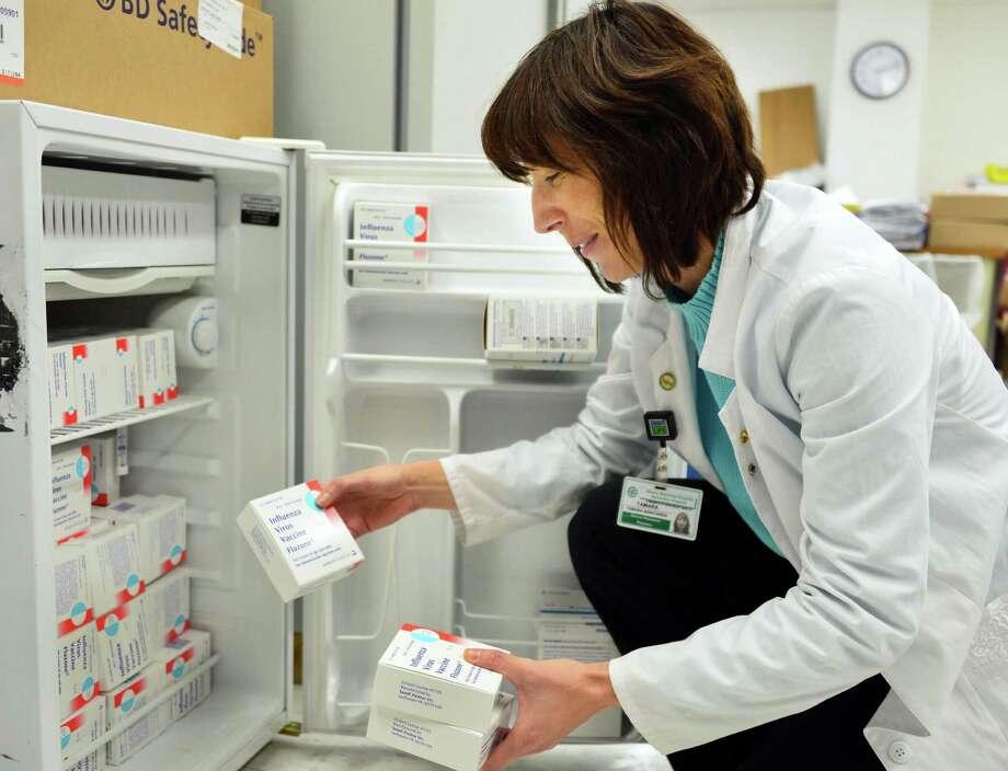 Clinical pharmacist Tamara Wanchisen restocks a cooler with flu vaccine Tuesday, Dec. 17, 2013, at Samaritan Hospital in Troy, N.Y.  (John Carl D'Annibale / Times Union) Photo: John Carl D'Annibale / 00025082A