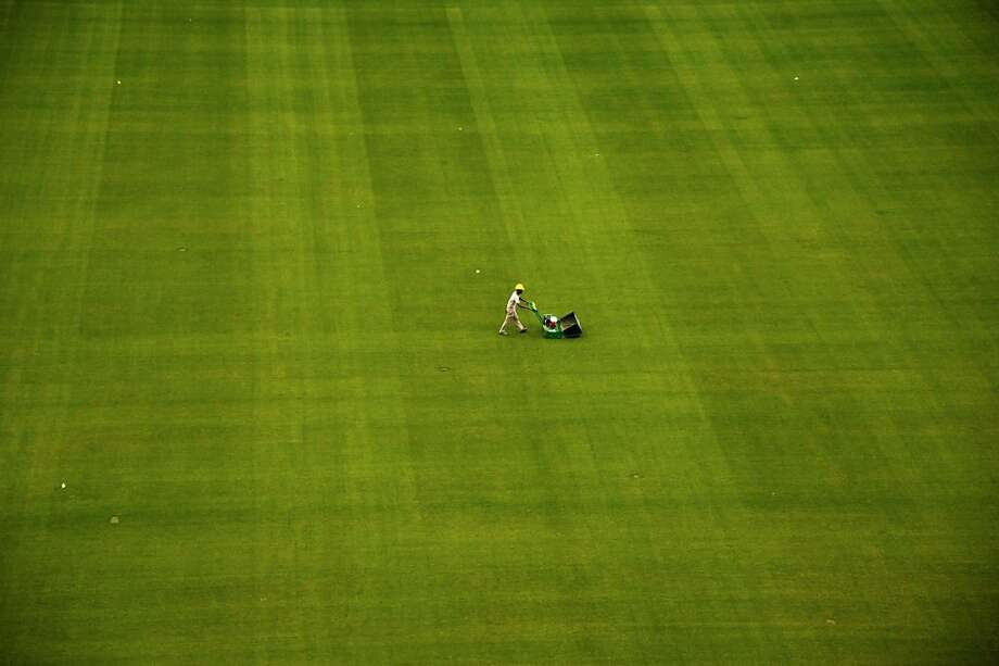 All I want for Christmas is a riding mower: A worker cuts the sprawling lawn of the Corinthians Arena in Sao Paulo, 