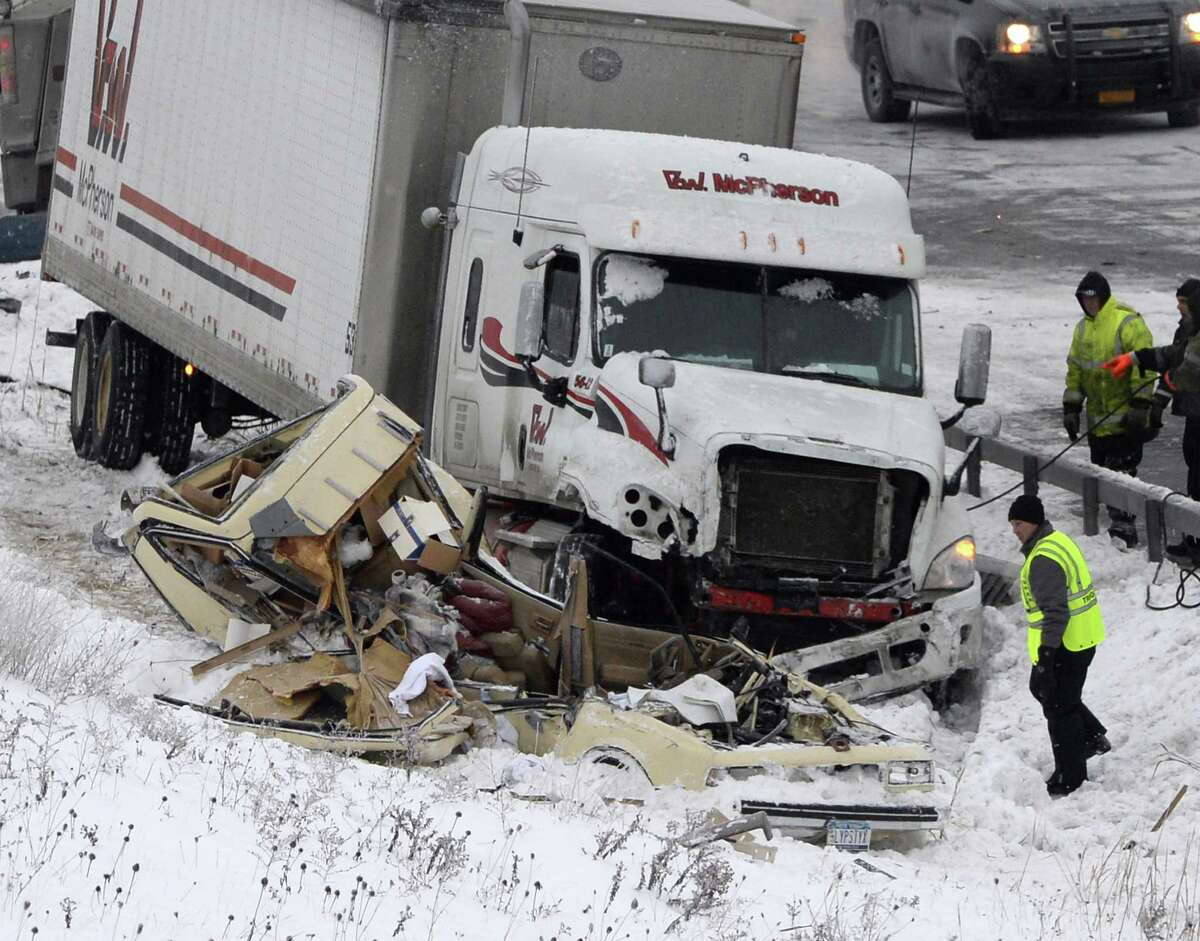 Workers and investigators continue the grim task of determining the cause of a Monday night accident Tuesday morning, Dec. 17, 2013, that killed trooper David Cunniff and injured another person on the Thruway in Amsterdam, N.Y. (Skip Dickstein / Times Union)