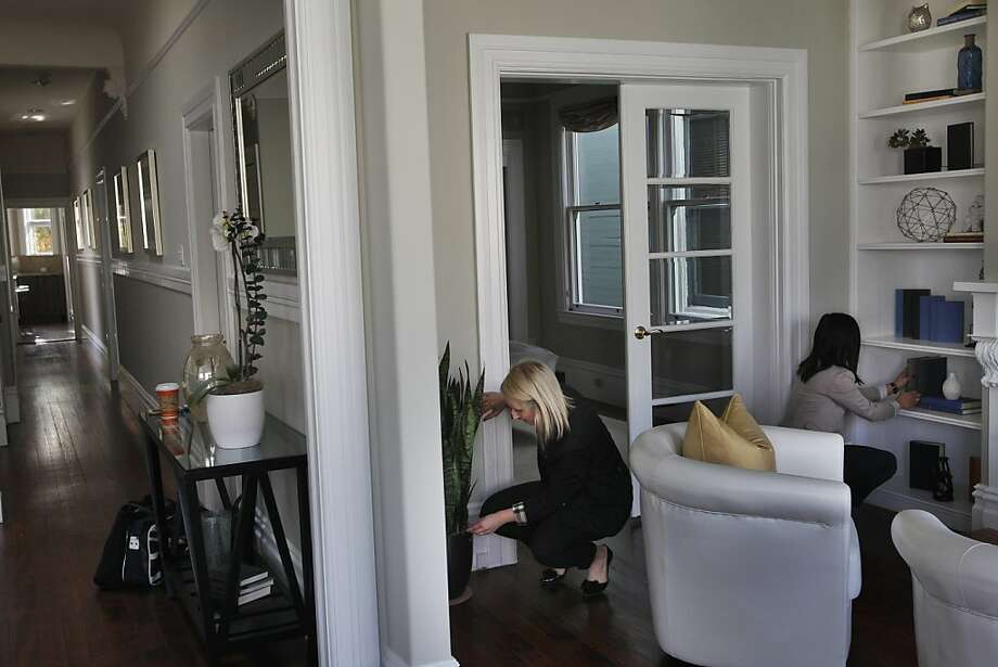 "Designers Tory Peterson, left, and Jennifer Chow make sure everything is picture perfect for a showing (a process they refer to as ""fluffing"") in a 2-bedroom, updated Edwardian style condo in Russian Hill December 17, 2013 in San Francisco, Calif. The designers from Design Milagros say that they will be back to ""fluff"" the place a few more times before it's put on the market. They also have a plant maintenance person who comes on a weekly basis to upkeep the live plants they provide as part of their staging. Photo: Leah Millis, The Chronicle"
