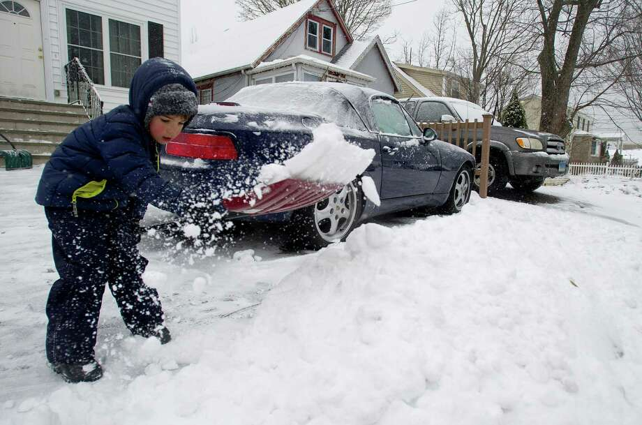 Peter Belov, 4, helps his mother, Natalia, shovel their driveway in Stamford, Conn., on Tuesday, December 17, 2013. Photo: Lindsay Perry / Stamford Advocate