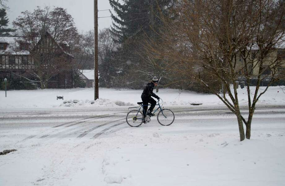 A bicyclist pedals through the snow in Stamford, Conn., on Tuesday, December 17, 2013. Photo: Lindsay Perry / Stamford Advocate