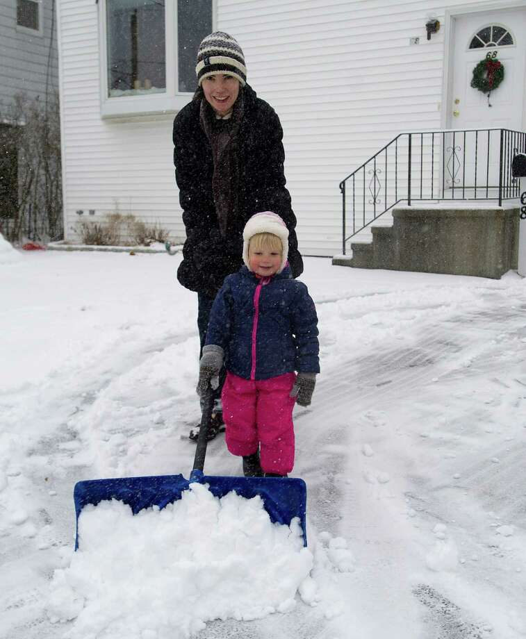 Natalia Belov and her daughter, Sasha, 2, shovel their driveway in Stamford, Conn., on Tuesday, December 17, 2013. Photo: Lindsay Perry / Stamford Advocate