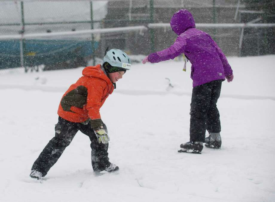 Tim Ryan, 8, left, and his sister, Ellen, 10, ice skate at a rink made on top of the tennis courts at the Stamford Yacht Club in Stamford, Conn., on Tuesday, December 17, 2013. Photo: Lindsay Perry / Stamford Advocate