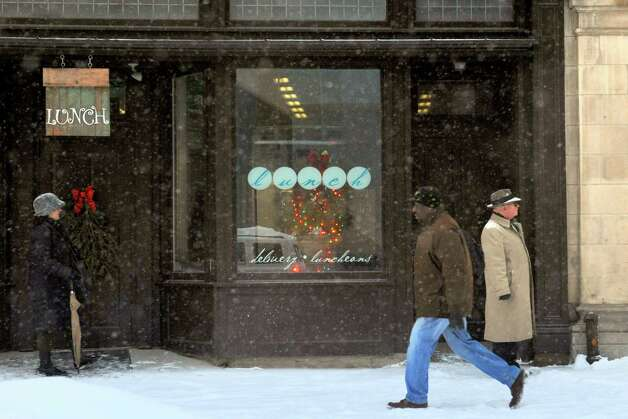 The end of the work day crowd wait for a bus or take to their feet as snow continues to fall on Broadway Tuesday Dec. 17, 2013 in Albany , N.Y. (Michael P. Farrell/Times Union) Photo: Michael P. Farrell / 00025077A