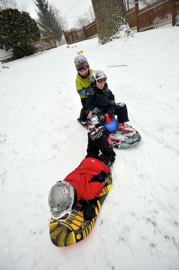 Ayden Mehl, bottom, sleds ahead of Jonah Hoff, top left, and Joreh Mehl in the Mehl's back yard in Stamford, Conn., on Tuesday, Dec. 17, 2013. Photo: Jason Rearick / Stamford Advocate