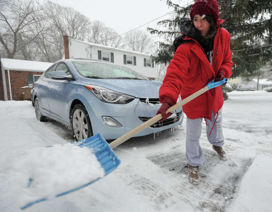 Lisa Michie clears her driveway of snow in Stamford, Conn., on Tuesday, Dec. 17, 2013. Photo: Jason Rearick / Stamford Advocate